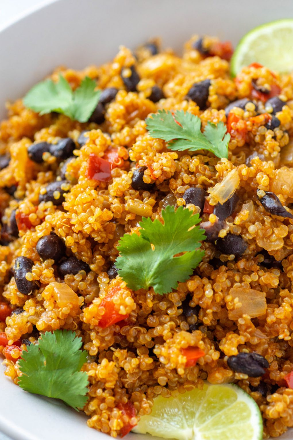 Super close up side angle shot of southwest quinoa with black beans, diced red pepper, fresh cilantro, and garnished with lime wedges. In a white bowl on a light colored background.