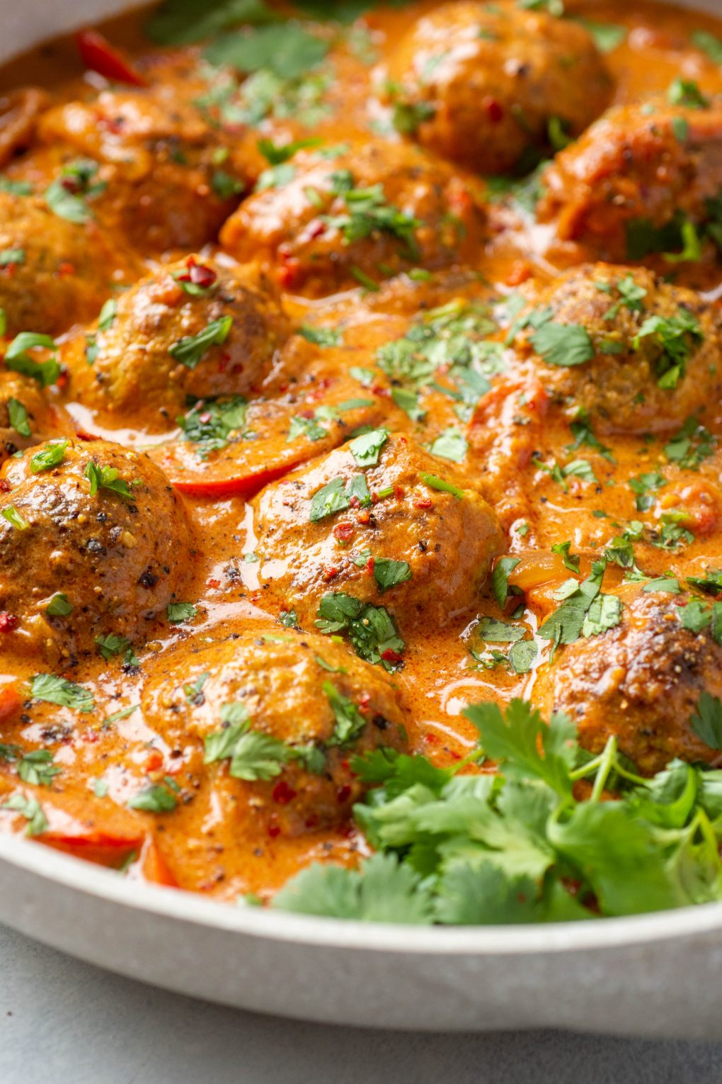 Close up side angle shot of a large white skillet filled with meatballs in a vibrant red curry sauce. Topped with chopped fresh cilantro.