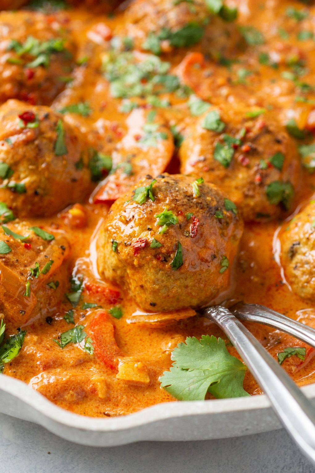 Close up side angle shot of a large white skillet filled with paleo meatballs in a vibrant red curry sauce. Topped with chopped fresh cilantro.
