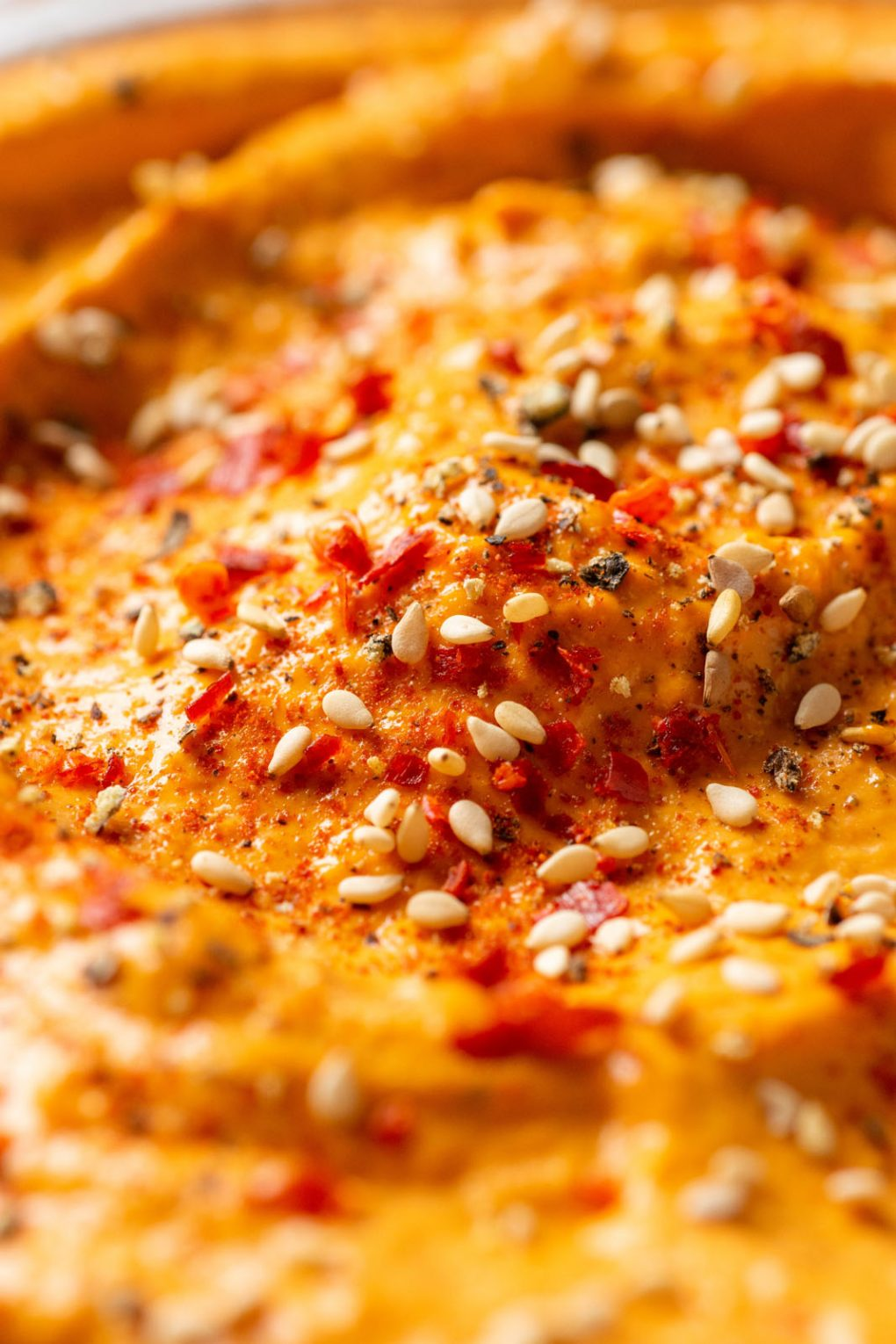 Macro close up shot of red pepper dip, sprinkled with sesame seeds and chili flakes.