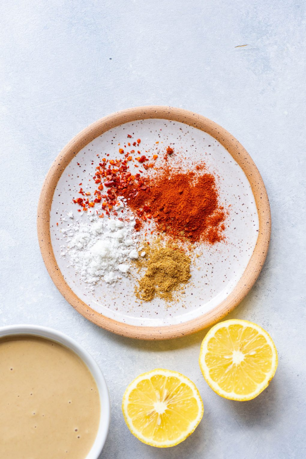 Overhead shot of a small round white plate with a brown rim with flaky sea salt, and an assortment of vibrant spices. On a white background next to a cut lemon and a small bowl of tahini.