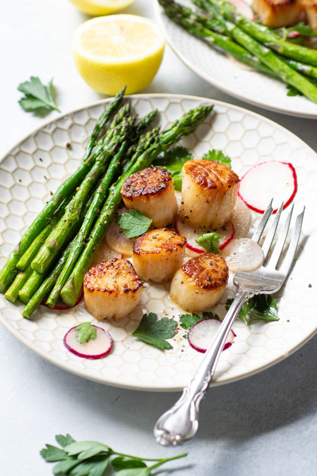 Side angle view of a white plate with seared scallops over a thinly sliced radish salad, next to a bundle of bright green asparagus. On a light background surrounded by a cut lemon and a scatter of fresh herbs.