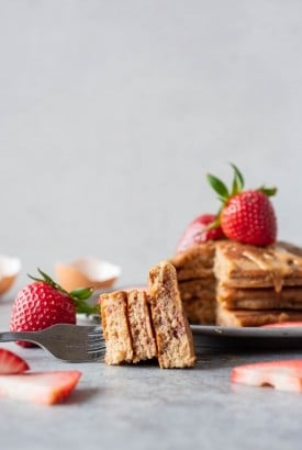 Side angle shot of a bit of pancakes on a fork, laying in front of a plate stacked with pancakes and fresh strawberries.