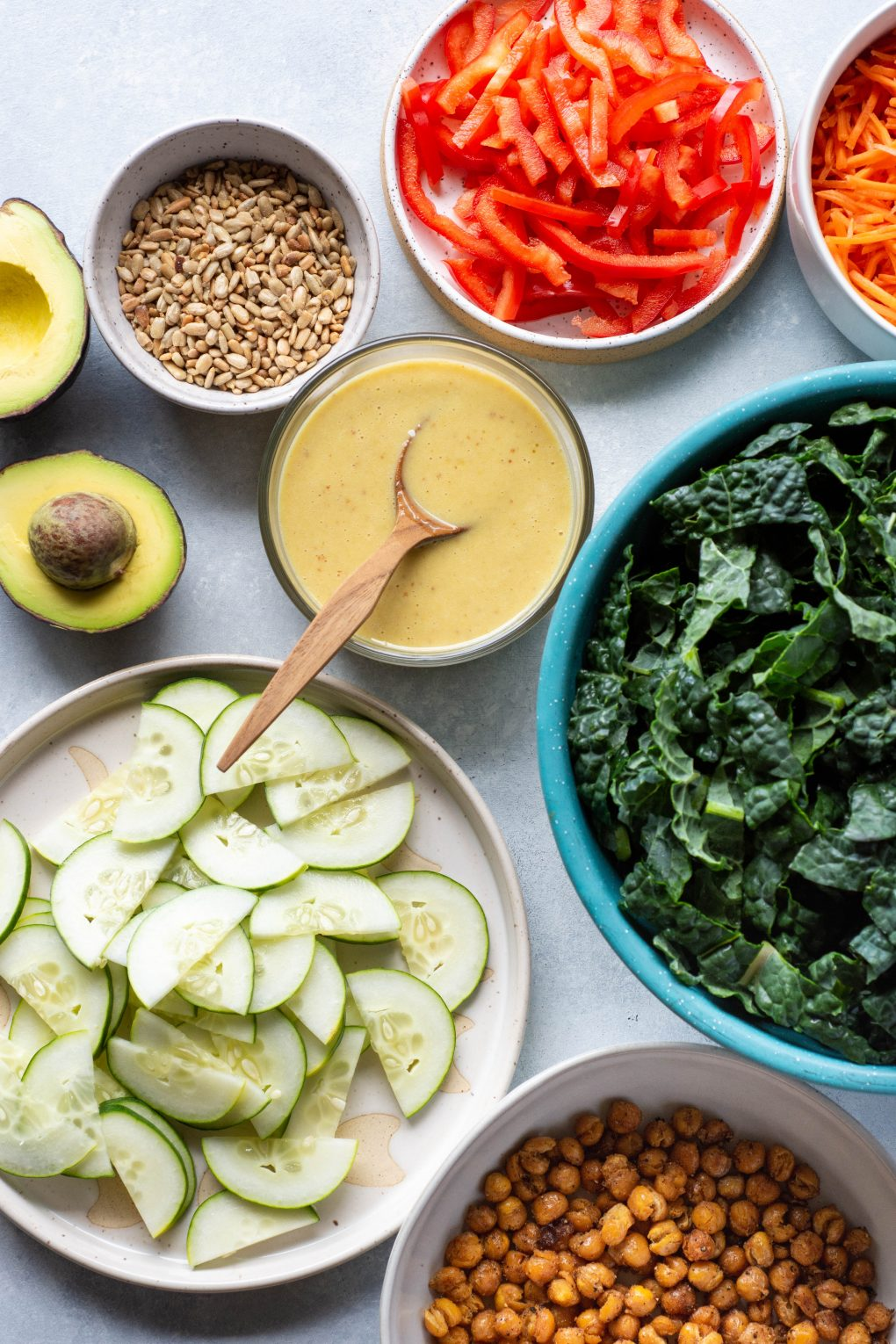 An assortment of bowls and plates filled with ingredients for a hearty kale salad - a bowl of kale, a plate of sliced cucumber, a bowl of honey mustard dressing, a bowl of sliced red pepper, a bowl of sunflower seeds, and a cut avocado. On a light colored background.