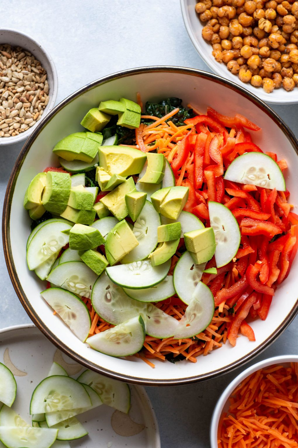 Overhead shot of a large white bowl filled with kale, shredded carrots, thinly sliced red pepper, thinly sliced cucumber, and avocado, on a light background