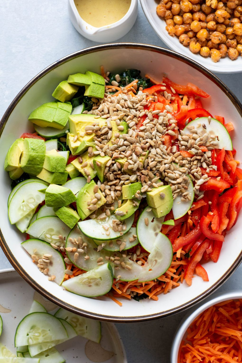 Overhead shot of a large white bowl filled with thinly sliced kale, sliced red pepper, shredded carrots, cucumbers cut into half moon slices, diced avocado, and roasted sunflower seeds. On a white background surrounded by a bowl of crispy chickpeas, a bowl of shredded carrots, and a plate of sliced cucumber.