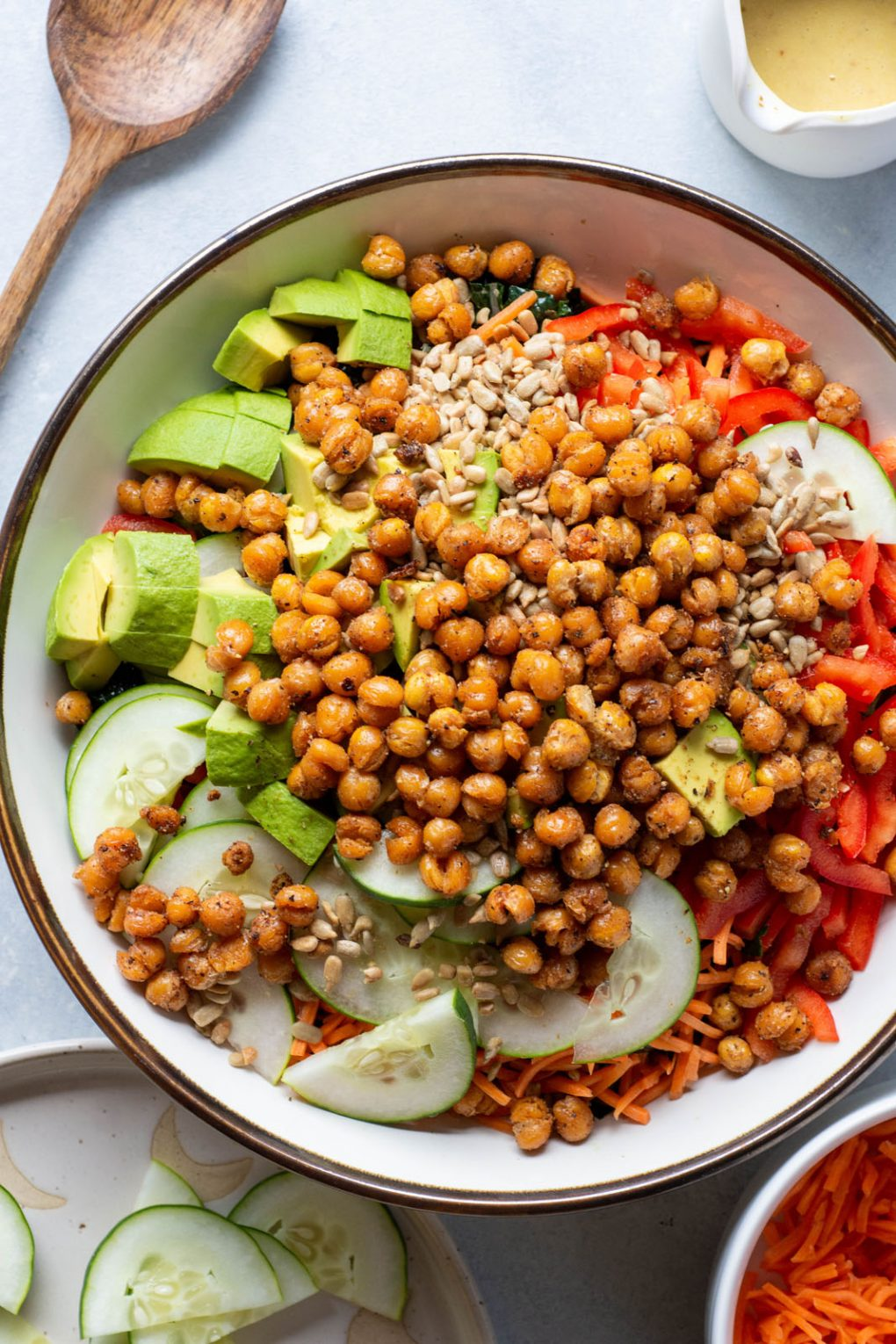 Overhead shot of a large white bowl filled with kale, shredded carrots, thinly sliced red pepper, thinly sliced cucumber, avocado, sunflower seeds, and crispy chickpeas, on a light background