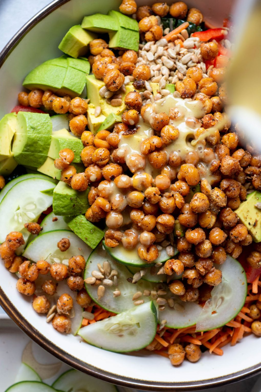 Close up over head shot of honey mustard dressing being poured over kale salad with crispy chickpeas.