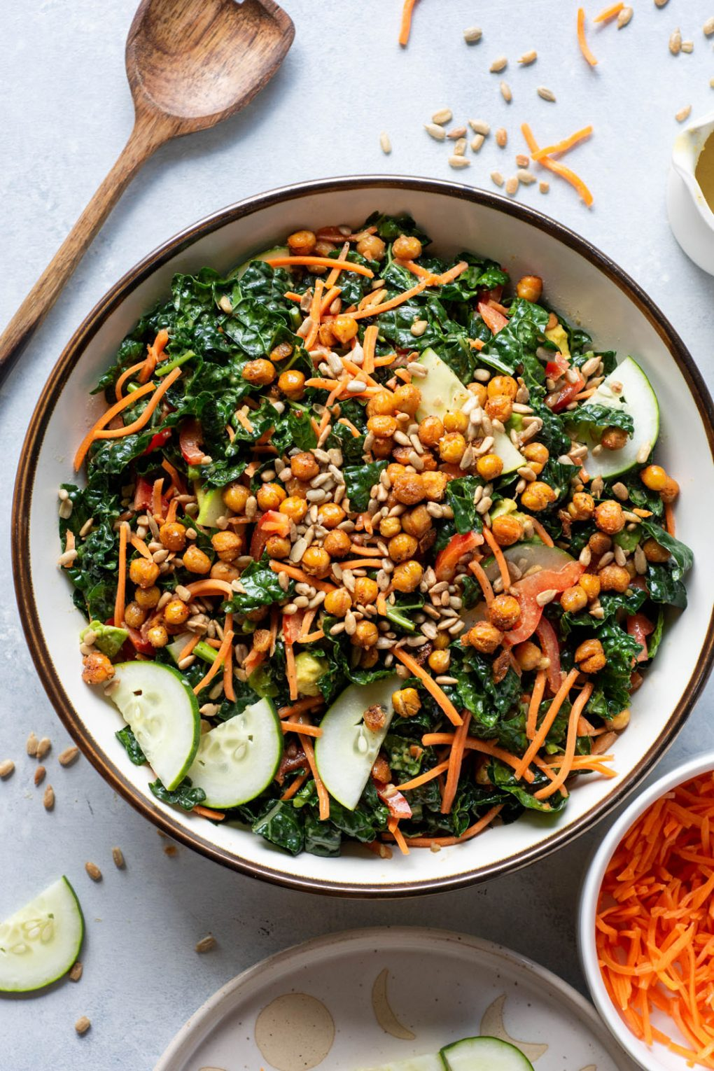 A large white bowl with hearty kale and chickpea salad all tossed together, on a light background next to a big wooden salad spoon and a bowl of shredded carrots.