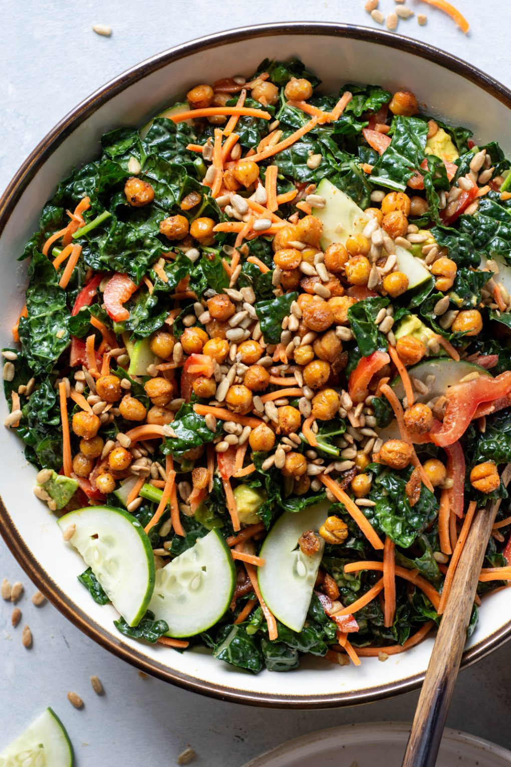 Close up overhead shot of kale salad with crispy chickpeas tossed all together. On a light background.