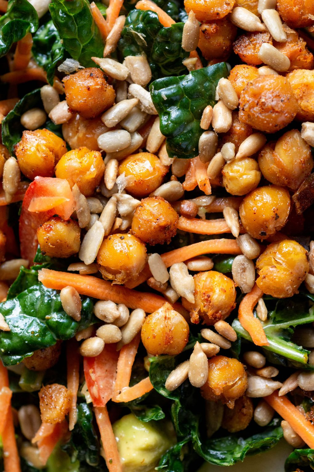 Super close up shot of chickpea and kale salad with shredded carrot and roasted sunflower seeds