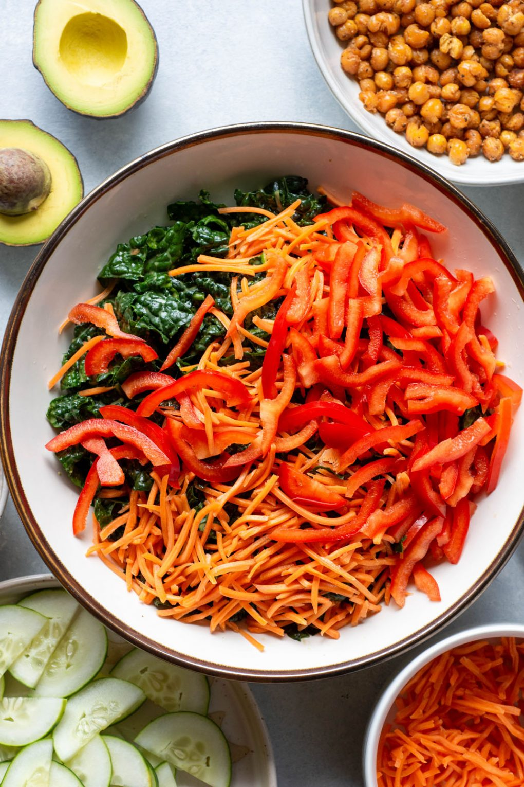 Overhead shot of a large white bowl filled with kale, shredded carrots, and thinly sliced red pepper on a light background