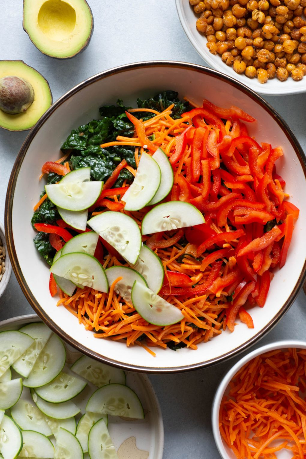 Overhead shot of a large white bowl filled with kale, shredded carrots, thinly sliced red pepper, and thinly sliced cucumber, on a light background