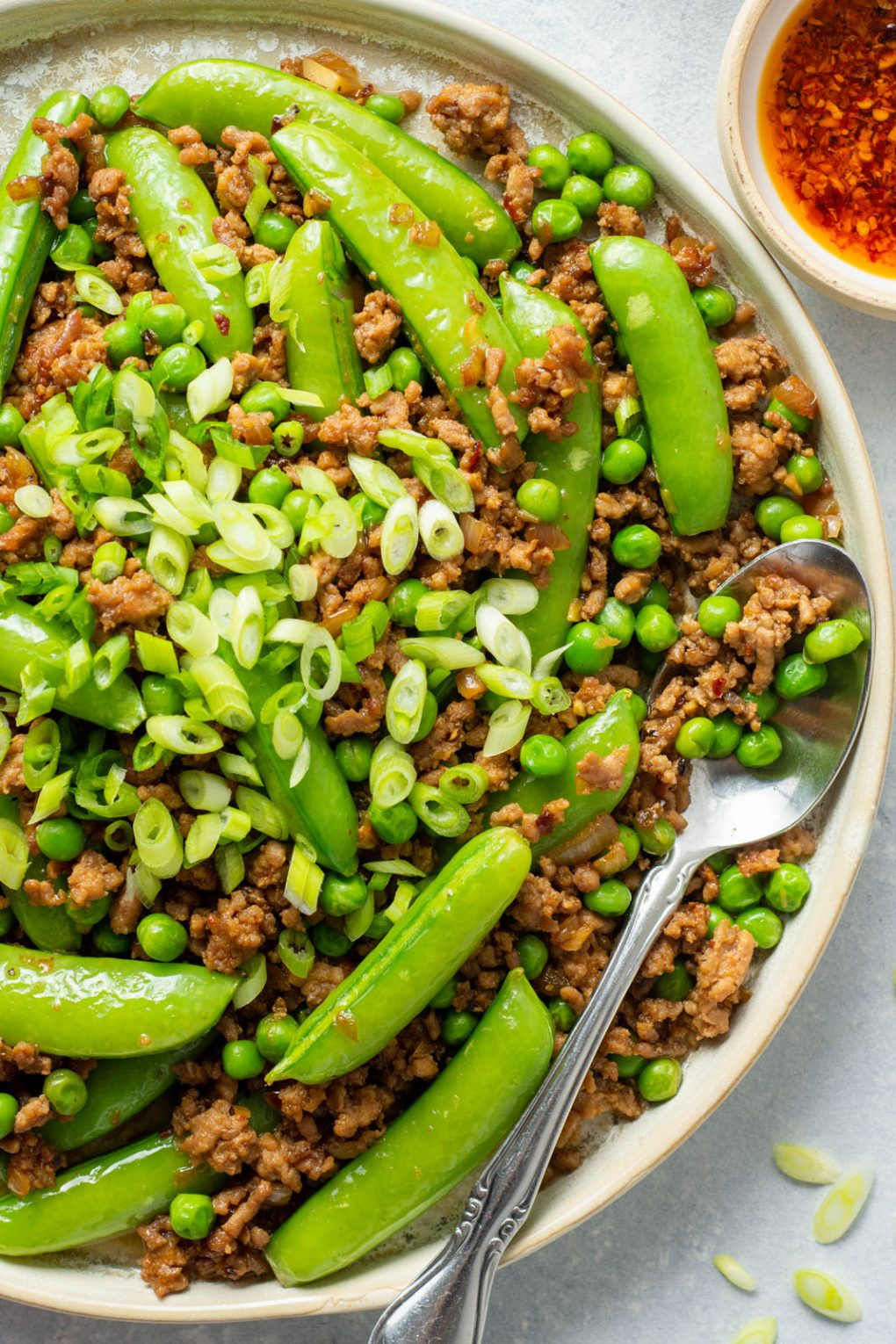 Super Up close shot of a round white rimmed ceramic plate filled with a crispy ground pork stir fry with green peas, sugar snap peas, and topped with plenty of green onions. A large silver spoon filled with stir fry is angled off the side of the plate. On a light colored background.