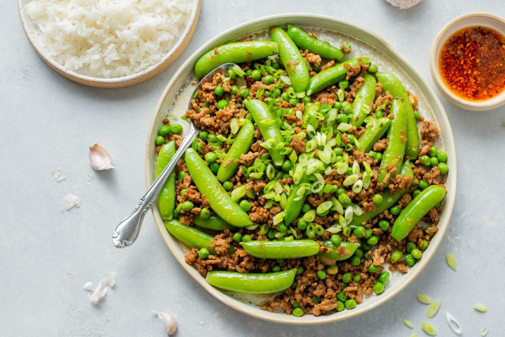 Overhead horizontal shot of a round white rimmed ceramic plate filled with ground pork stir fry with green peas, sugar snap peas, and topped with plenty of green onions. A large silver spoon filled with stir fry is angled off the side of the plate. On a light colored background, next to a small bowl of white rice, and a little mini bowl of bright red chili oil.