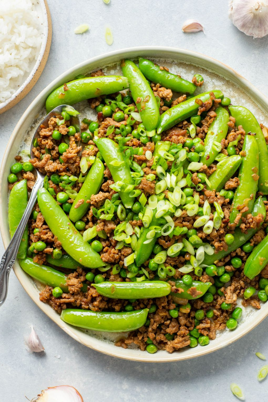 Up close shot of a round white rimmed ceramic plate filled with a crispy ground pork stir fry with green peas, sugar snap peas, and topped with plenty of green onions. A large silver spoon filled with stir fry is angled off the side of the plate. On a light colored background.
