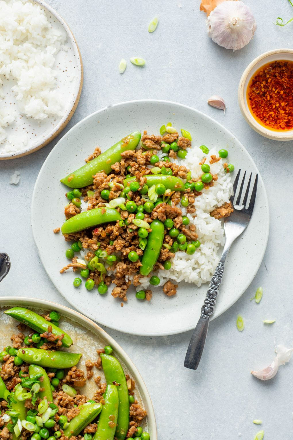 Overhead shot of a small white speckled plate with white rice, and a healthy portion of a crispy pork stir fry with green peas and sugar snap peas. A small decorative silver fork is on the plate, and it's on a light colored background next to a bowl of rice, a larger plate filled with saucy stir fry, and a small bowl of bright red chili oil.