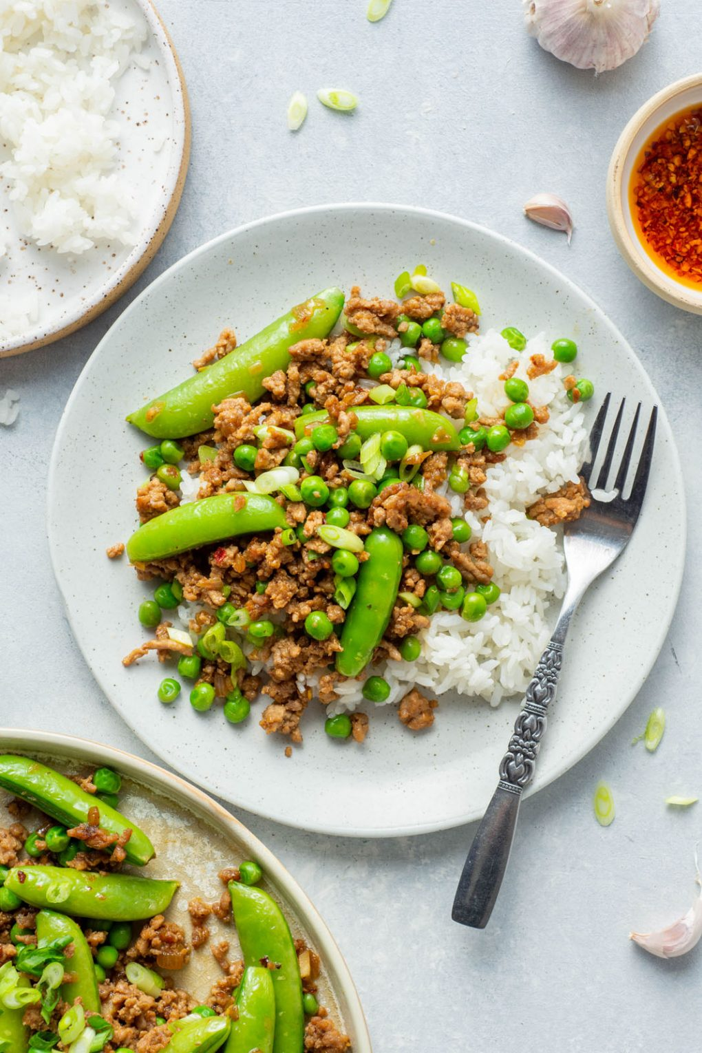 Up close overhead shot of a small white speckled plate with white rice, and a healthy portion of pork stir fry with green peas and sugar snap peas. A small decorative silver fork is on the plate, and it's on a light colored background next to a bowl of rice, and a small bowl of bright red chili oil.