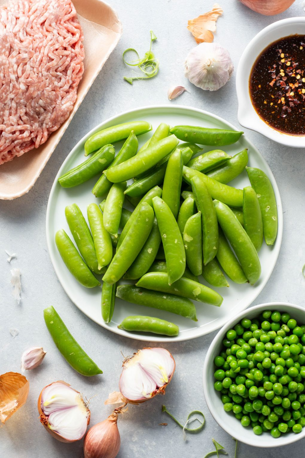 Overhead shot of all the ingredients needed to make a super easy 30 minute crispy ground pork stir fry. There's a large round white plate of peas in the center, surrounded by a little plate with green peas, some shallots cut in half, garlic cloves, a small bowl of chili oil, and an opened package of ground pork.