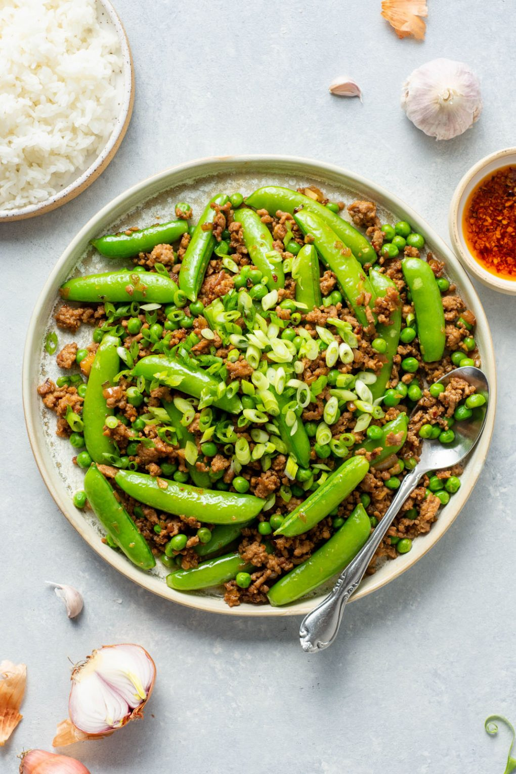 Overhead shot of a round white rimmed ceramic plate filled with a ground pork stir fry with green peas, sugar snap peas, and topped with plenty of green onions. A large silver spoon filled with stir fry is angled off the side of the plate. On a light colored background, next to a small bowl of white rice, a little mini bowl of bright red chili oil, shot cut shallots and garlic cloves.