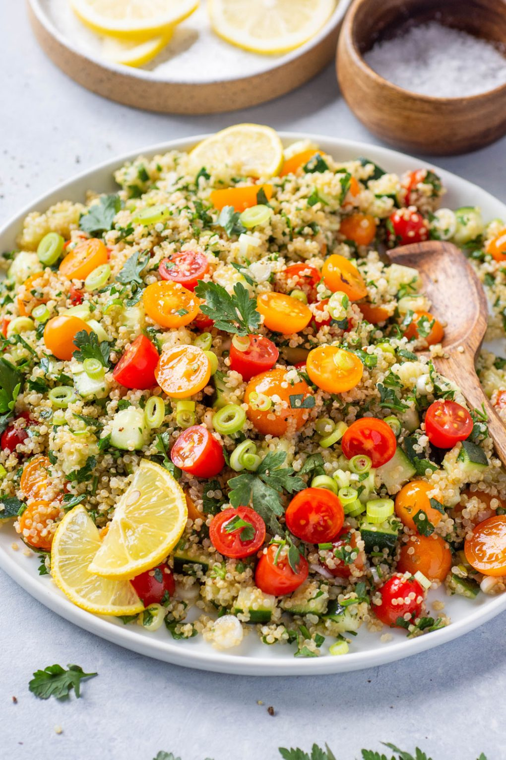 45 degree angle shot a large colorful plate of quinoa tabbouleh with red and orange cherry tomatoes, cucumber, parsley, and green onions. Garnished with a few lemon wedges on a light colored background surrounded by some scattered herbs and cherry tomatoes.