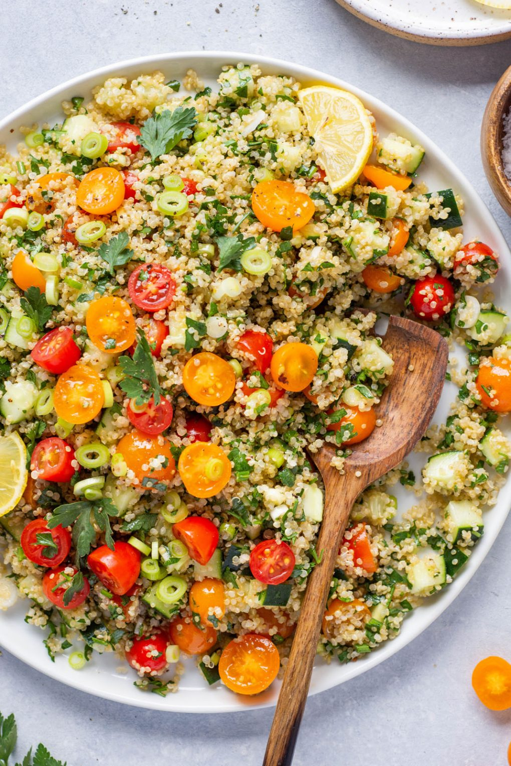 Overhead shot of a large colorful plate of quinoa tabbouleh with red and orange cherry tomatoes, parsley, green onions, and cucumber. Large wooden spoon placed at an angle on the white plate.