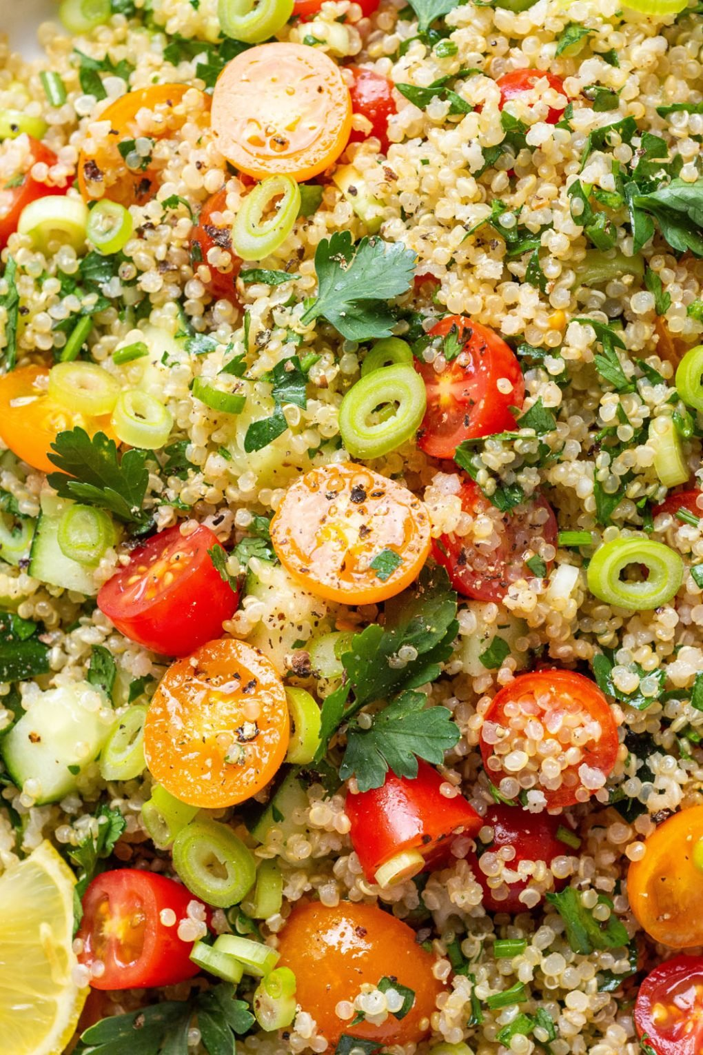Super up close shot of gluten free quinoa tabbouleh with glistening olive oil and freshly cracked black pepper.