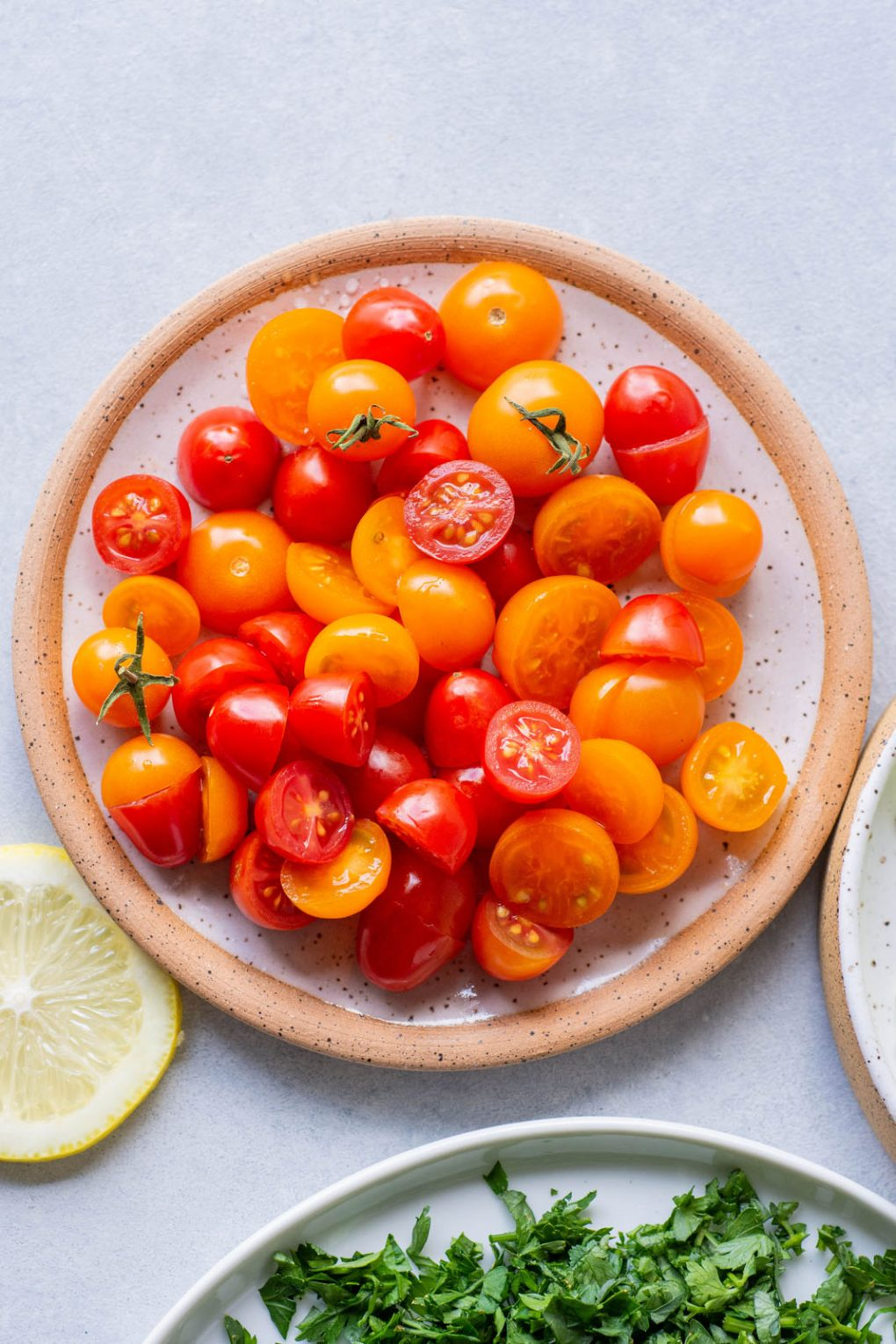 Upclose overhead shot of a speckled white plate filled with red and orange cherry tomatoes. On a light colored background.