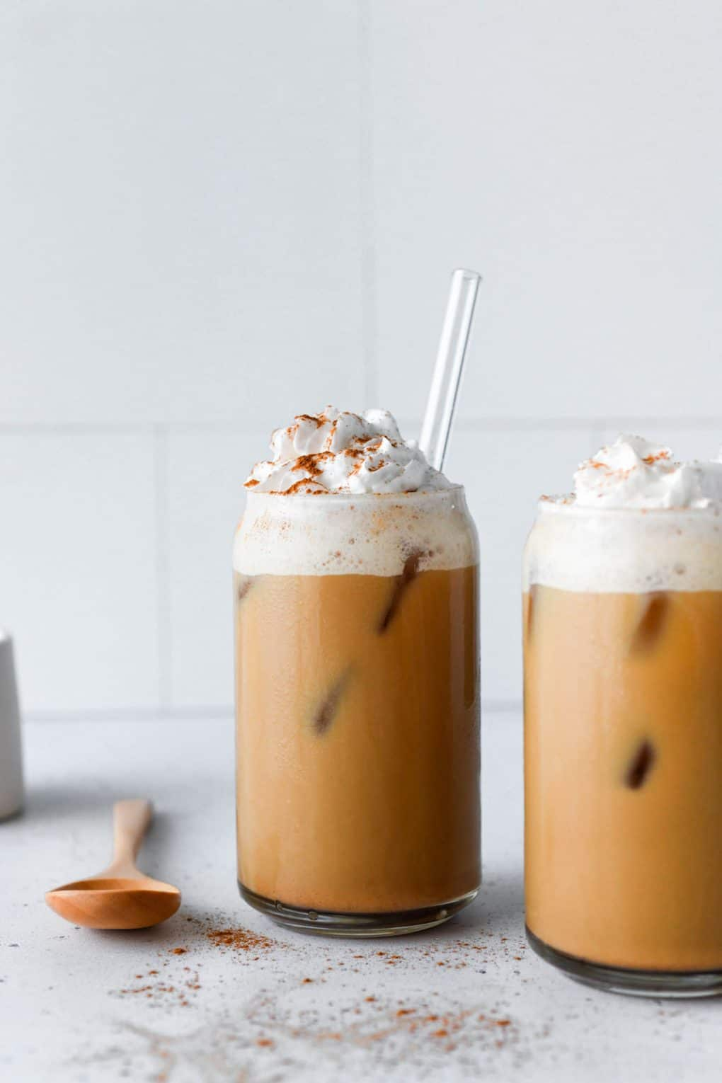 Straight on shot of two side by side iced pumpkin spice lattes topped with lots of whipped cream and a dash of pumpkin pie spice. On a light colored background with a small wooden spoon in the background.