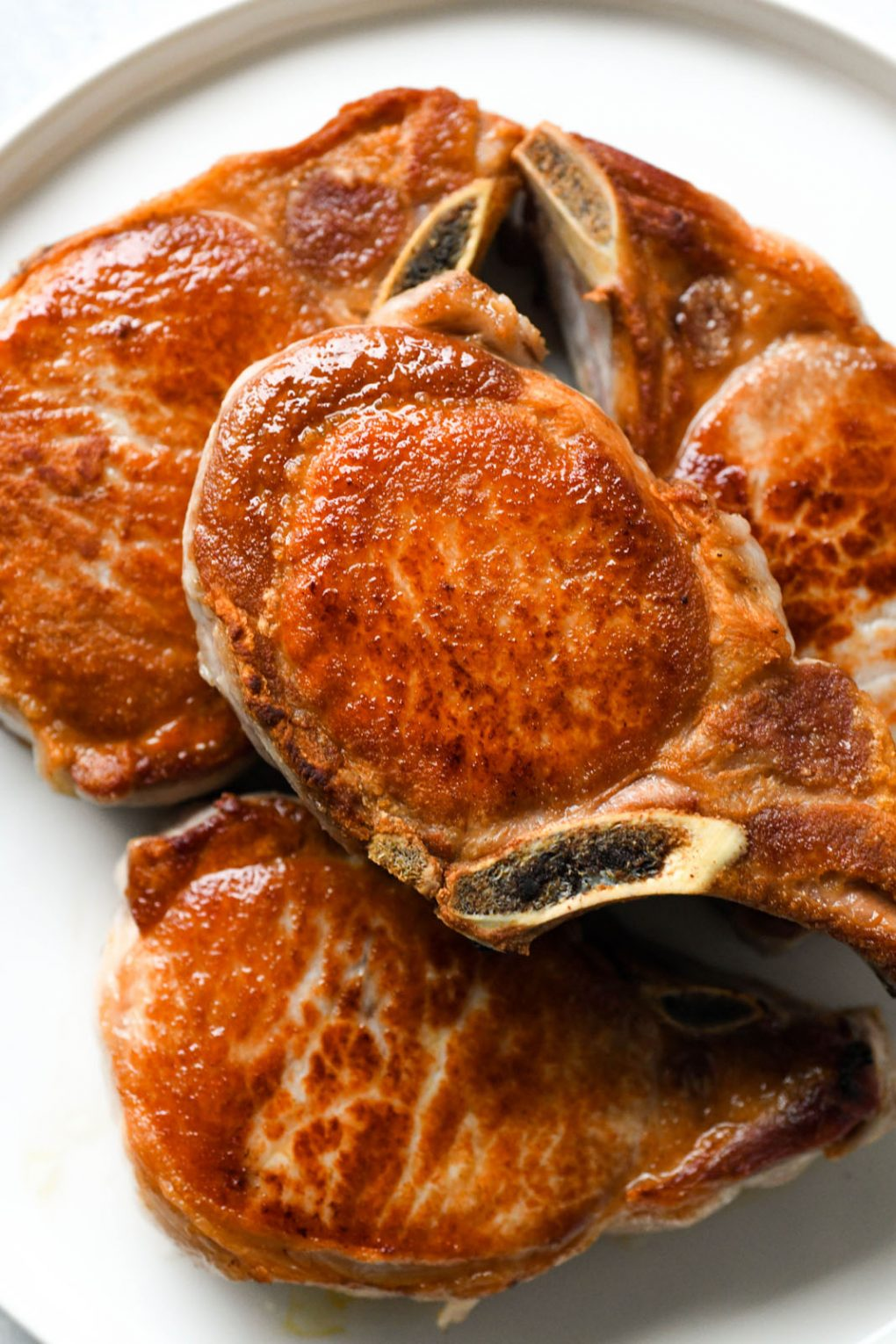 Overhead shot of a plate of pan seared bone in pork chops. Cooked to a perfect golden brown on a light colored background.