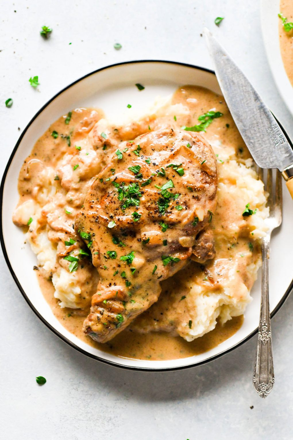 Overhead shot of a smothered pork chop on a plate over mashed potatoes topped with plenty of gravy. Garnished with chopped green parsley on a light colored background.