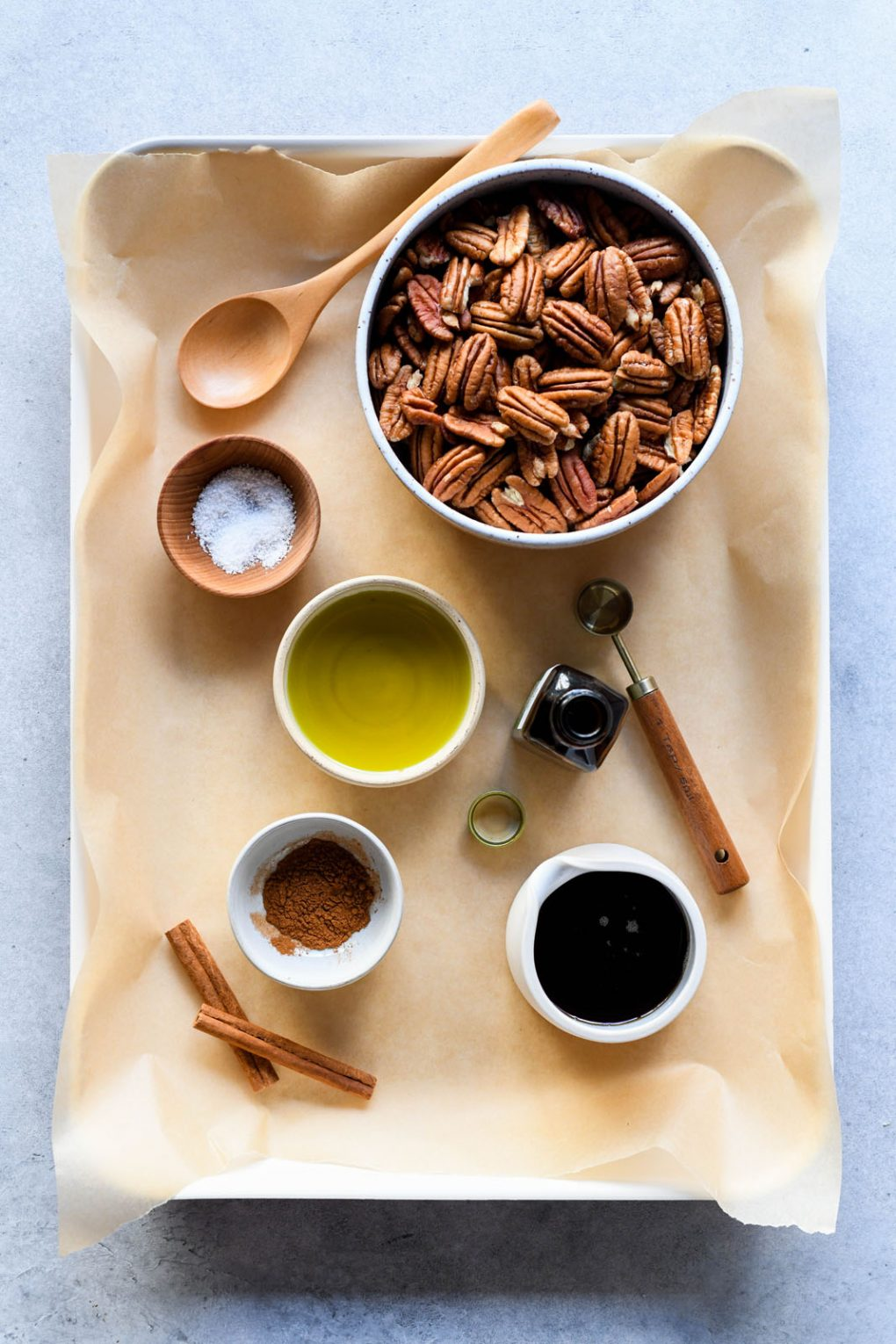 Overhead view of a baking sheet lined with parchment paper, filled with the ingredients for candied pecans in small dishes - raw pecans, sea salt, avocado oil, cinnamon, maple syrup, and vanilla extract.