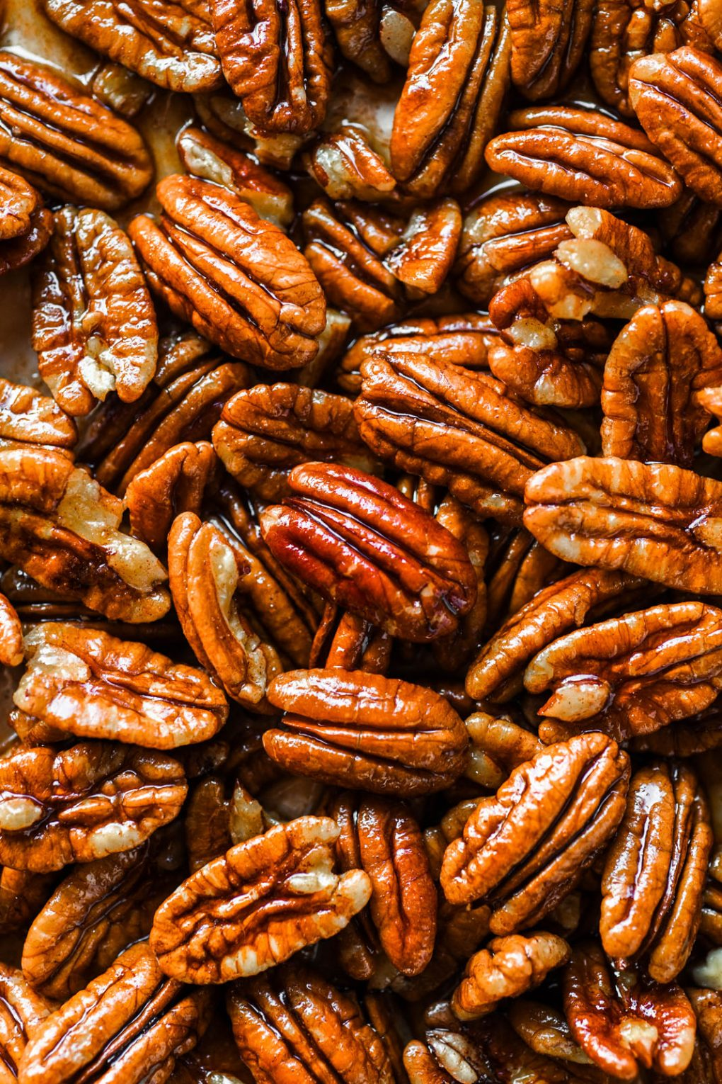 Macro shot of raw pecans glistening with maple syrup and cinnamon mixture.