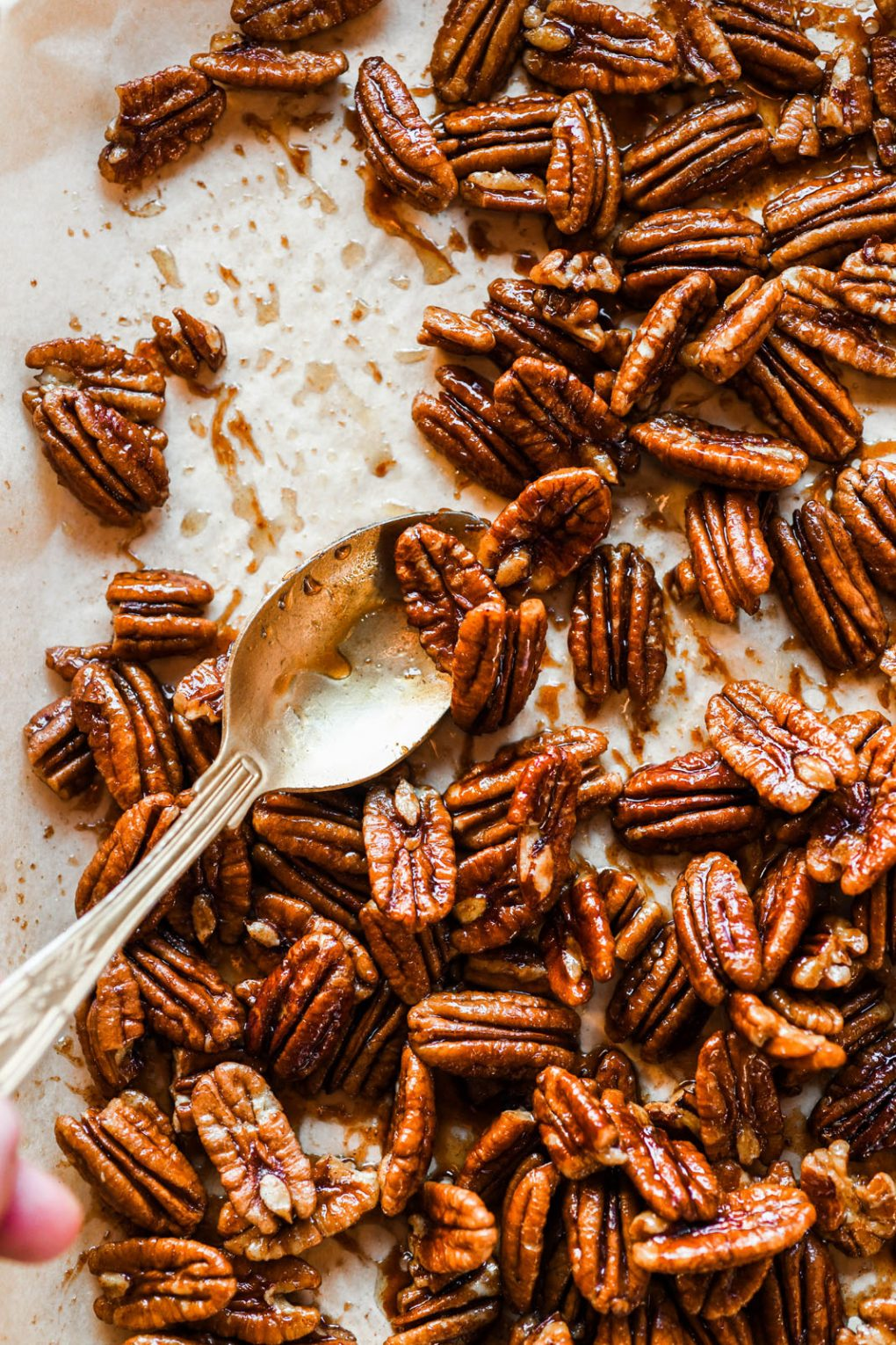Overhead view of a spoon scraping sticky candied pecans onto one side of a parchment lined baking sheet.