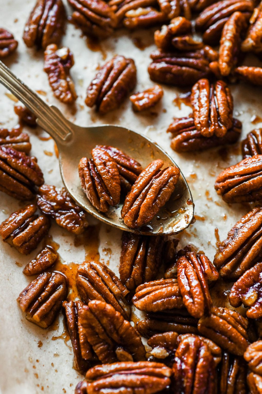 Close up shot of a few candied pecans sitting on a gold spoon, on a parchment lined baking sheet surrounded by scattered candied pecans.