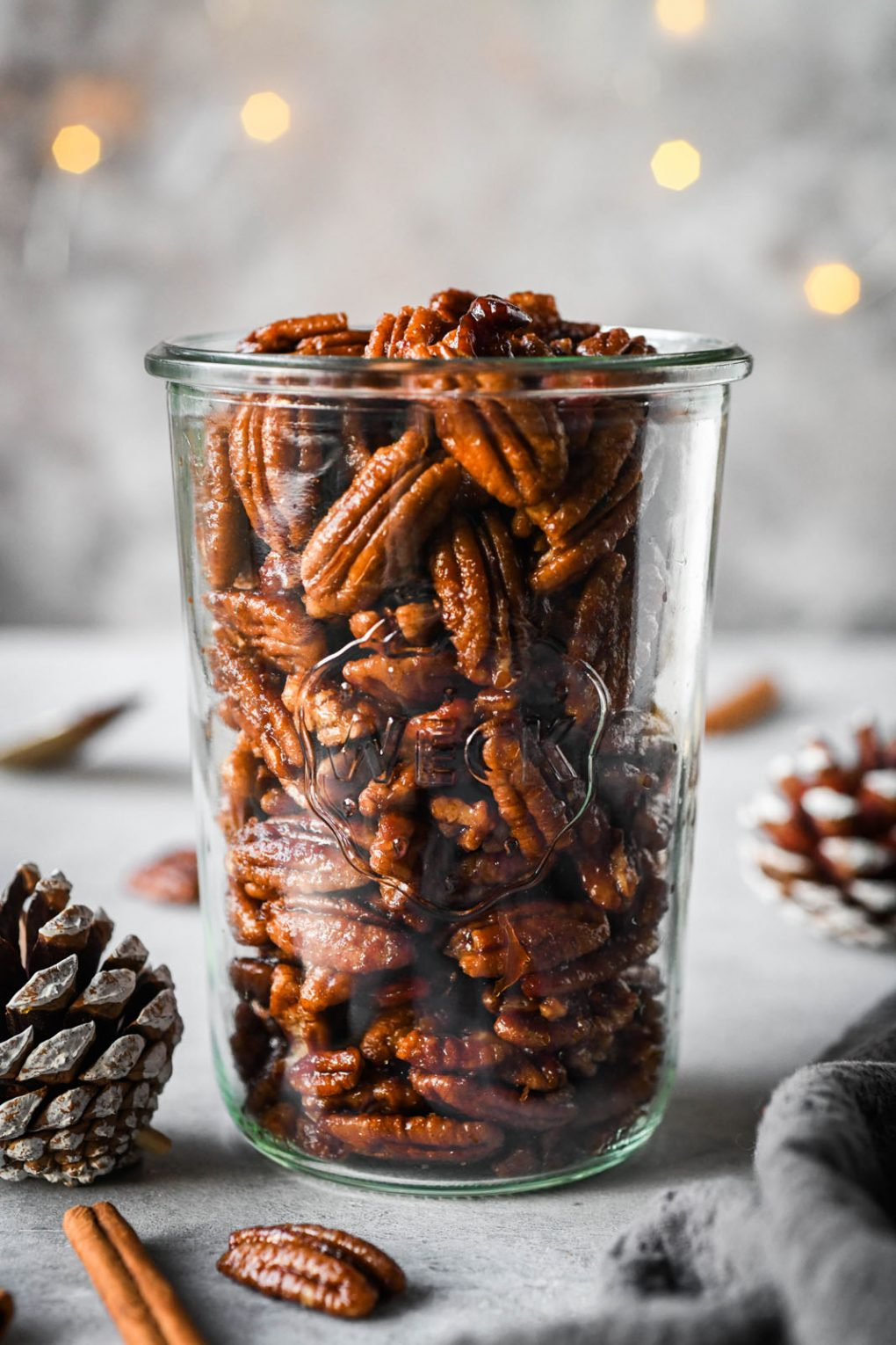 Close up shot of a tall weck jar filled with candied pecans. With a dark grey background, surrounded by a few festive pinecones and cinnamon stick.