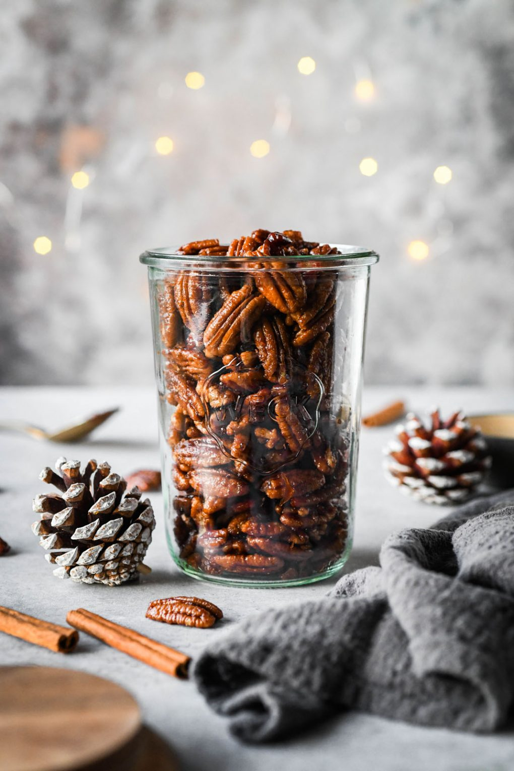 Straight on shot of a tall weck jar filled with candied pecans. With a dark grey background, surrounded by a few festive pinecones and cinnamon stick.