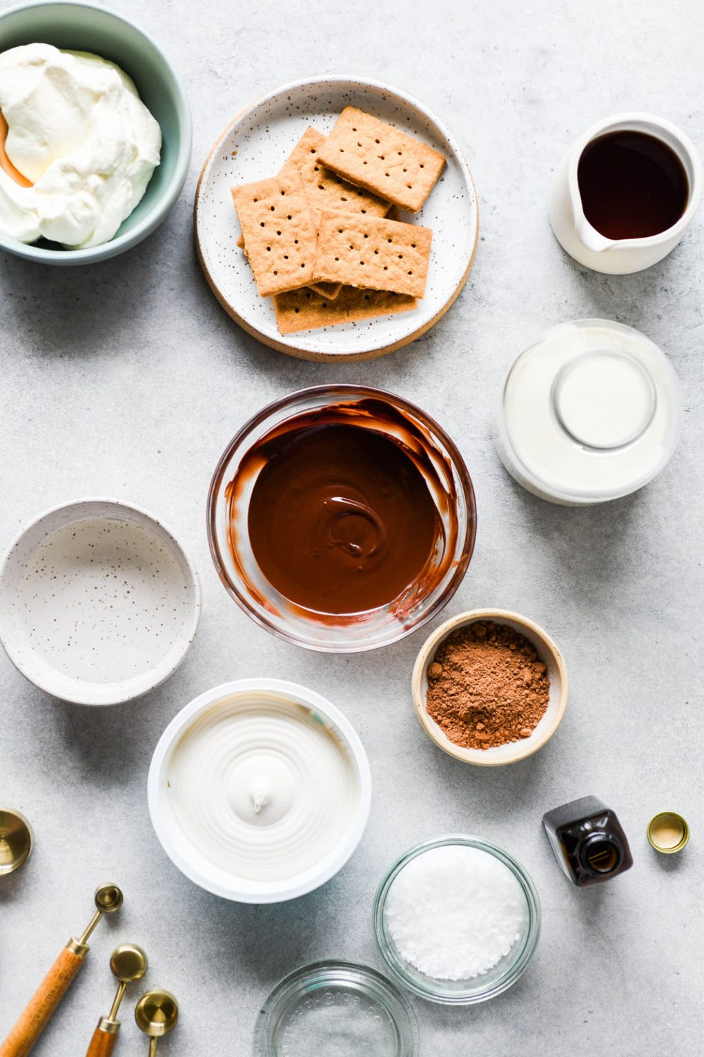 A flat lay of all the ingredients needed to make vegan chocolate mousse. Graham crackers, melted chocolate, non dairy milk, cacao powder, dairy free cream cheese, coconut oil, vanilla, sea salt, and whipped cream.
