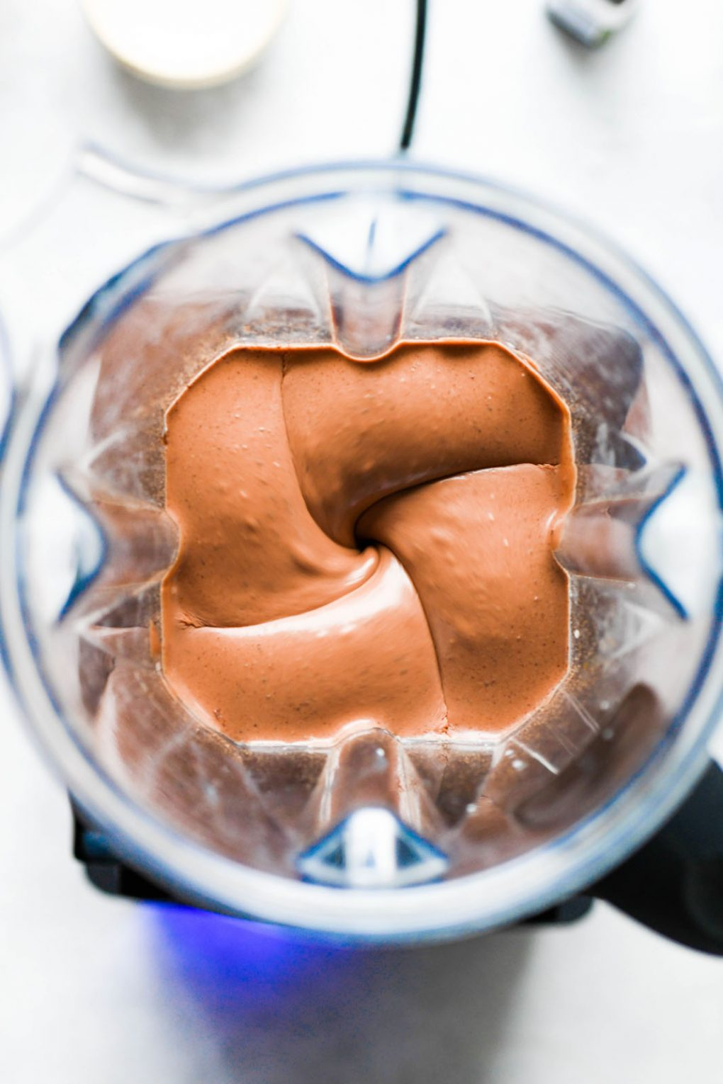 Overhead view of vegan chocolate mousse whirring in a blender.