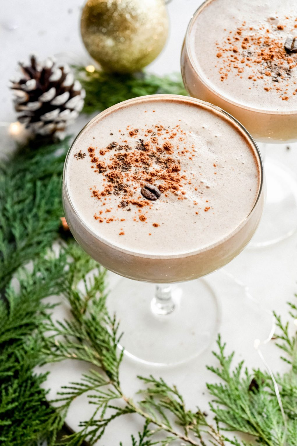 45 degree angle shot of a creamy eggnog espresso martini. Topped with cinnamon and a coffee bean. On a light colored background surrounded by some cedar branches, pine cones, and tiny little white string lights.
