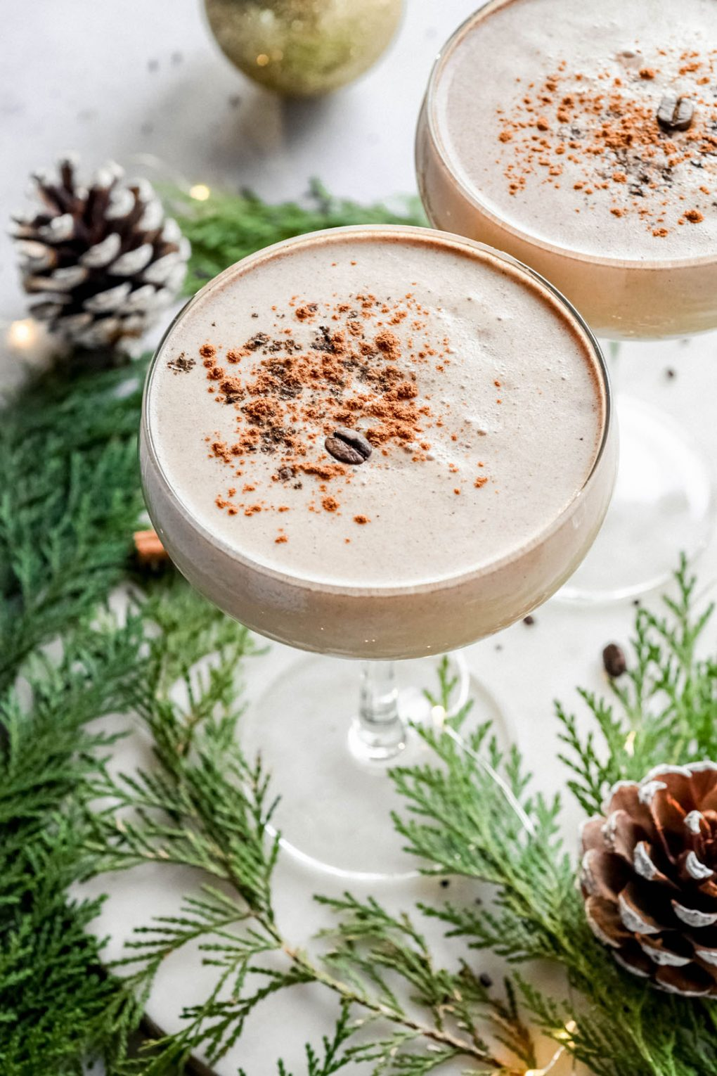 Close up view of a creamy eggnog espresso martini in a coupe glass. Topped with a dash of cinnamon and a coffee bean. On a white background surrounded by cedar, pine cones and tiny little string lights.