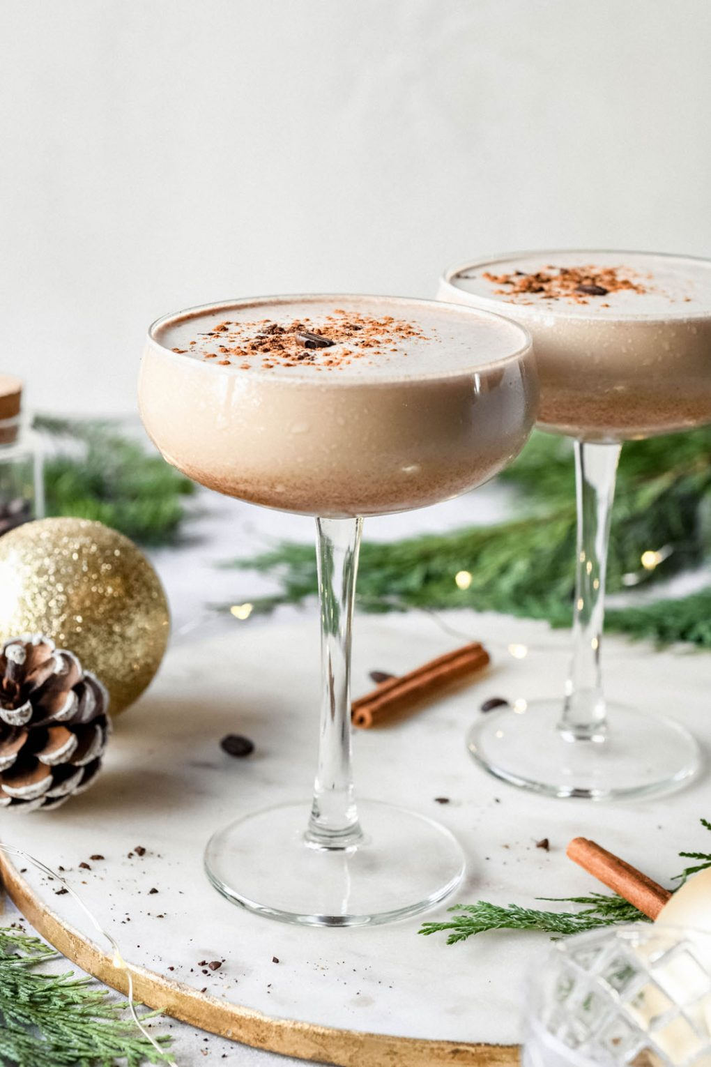 Straight on shot of two creamy eggnog espresso martinis topped with cinnamon and coffee beans. On a light background, next to a pine cone, some green cedar branches, a sparkly christmas tree ornament, and a few cinnamon sticks.
