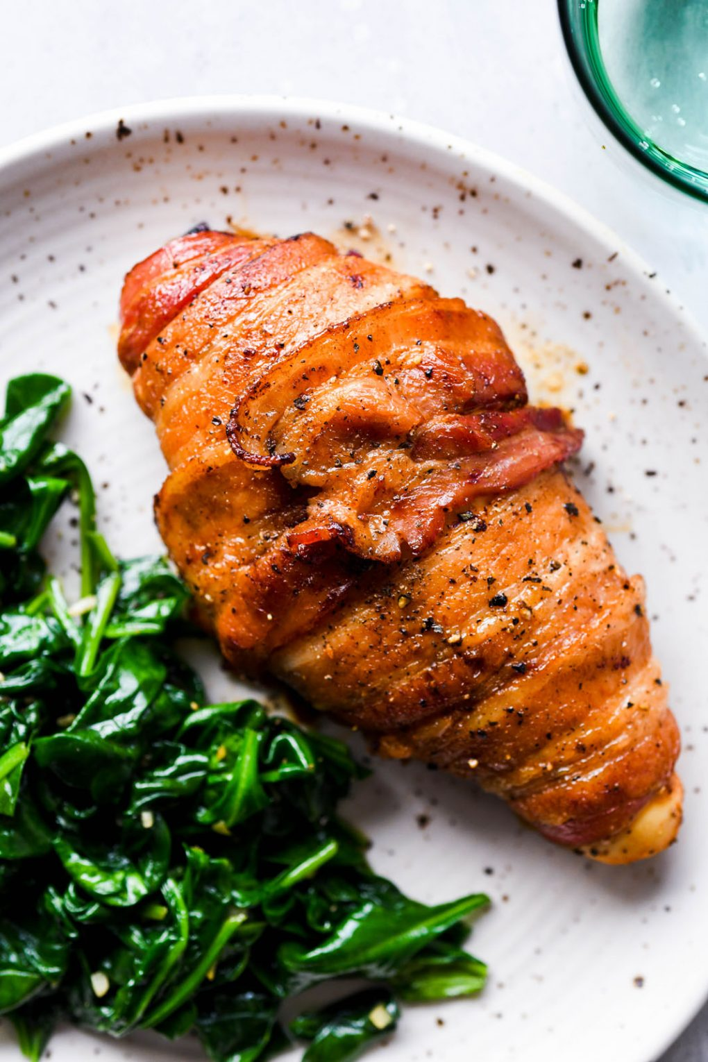 Close up image of a glistening bacon wrapped chicken breast, on a white speckled plate next to some wilted garlic spinach with a light green glass of sparkling water peeking into the corner of the frame.