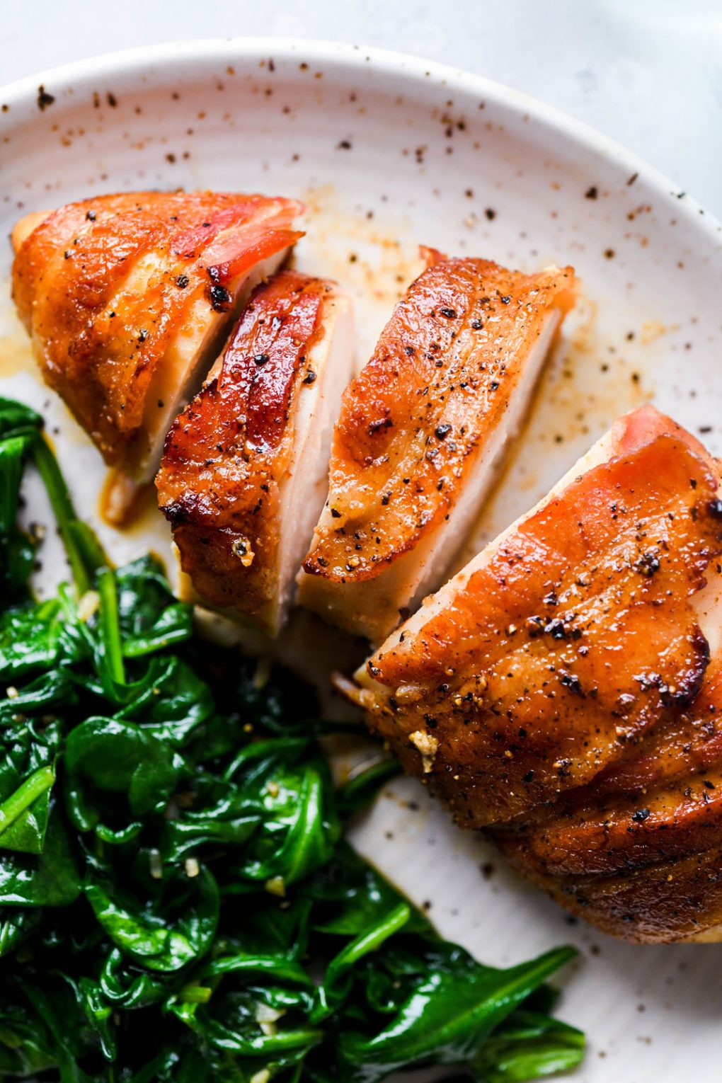 Close up image of a glistening bacon wrapped chicken breast cut into slices, on a white speckled plate next to some wilted garlic spinach.