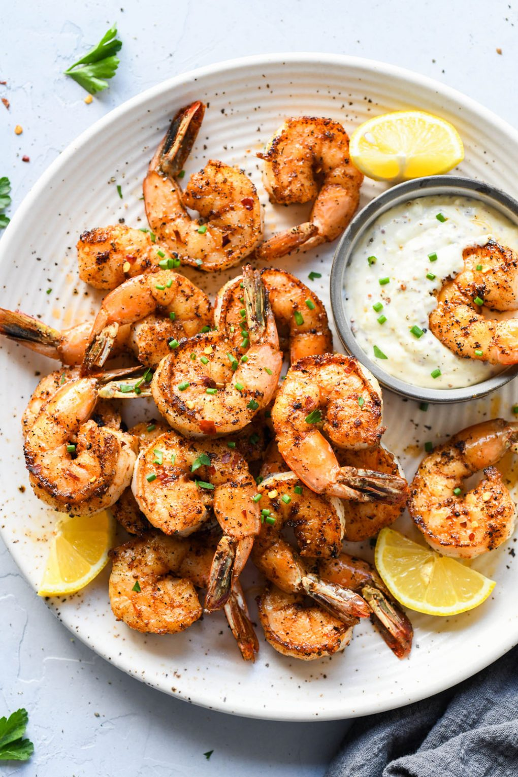 Light speckled plate of cajun spiced shrimp topped with snipped chives. Lemon wedges on the plate and a small bowl of aioli.