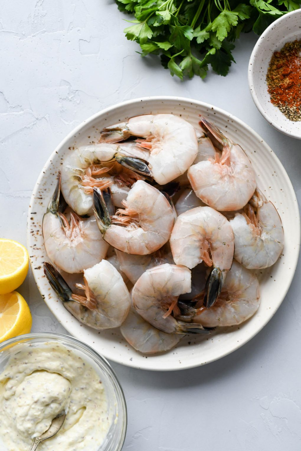 Picture of the ingredients for Whole30 cajun spiced shrimp - plate of raw shell on shrimp, small bowl of aioli, a few lemon wedges, a small bowl filled with spice blend, and a bundle of fresh herbs.
