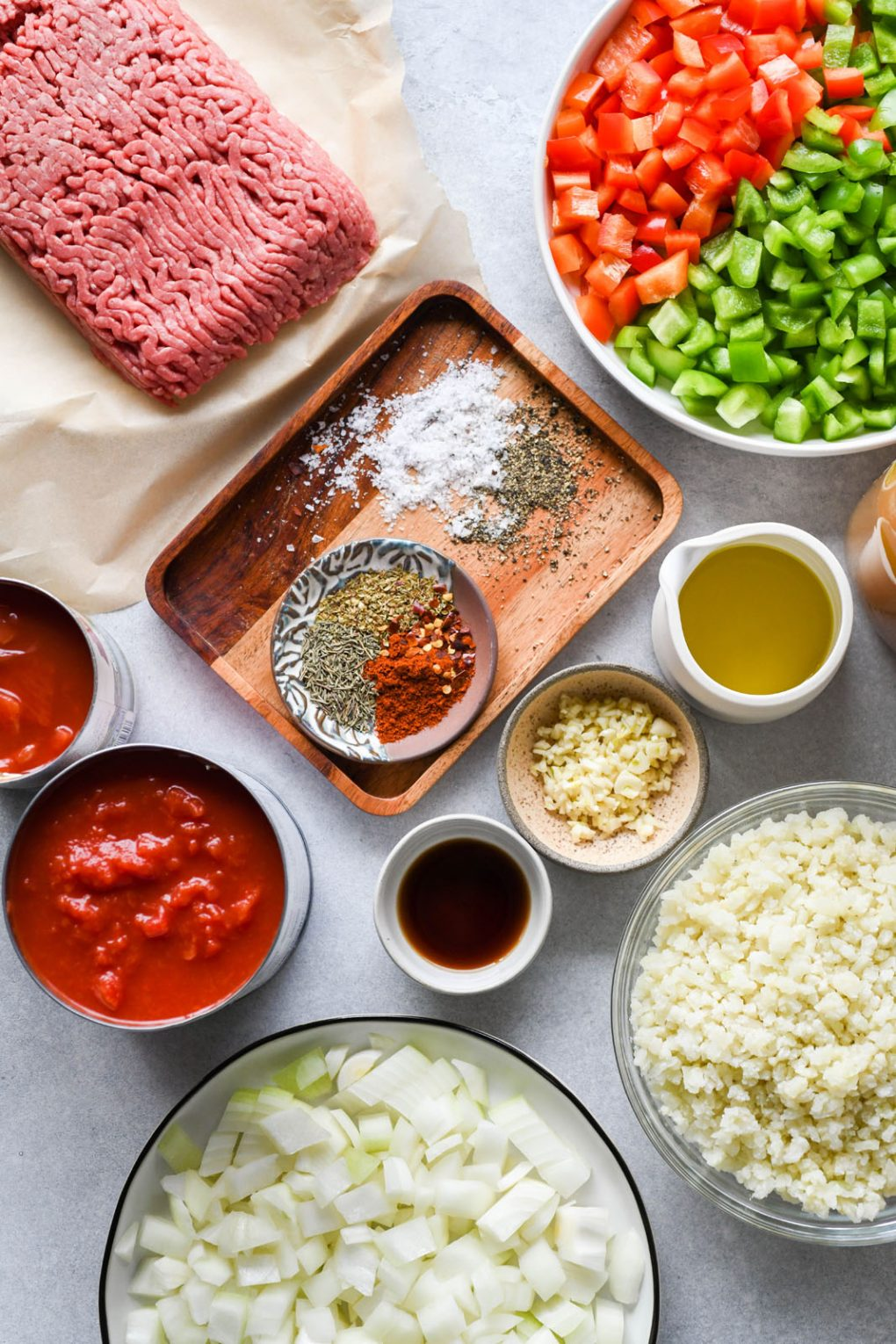 Overhead shot of the ingredients for stuffed pepper soup - Canned tomatoes, diced onions, diced bell peppers, ground beef, spices, olive oil, and cauliflower rice. On a light background.