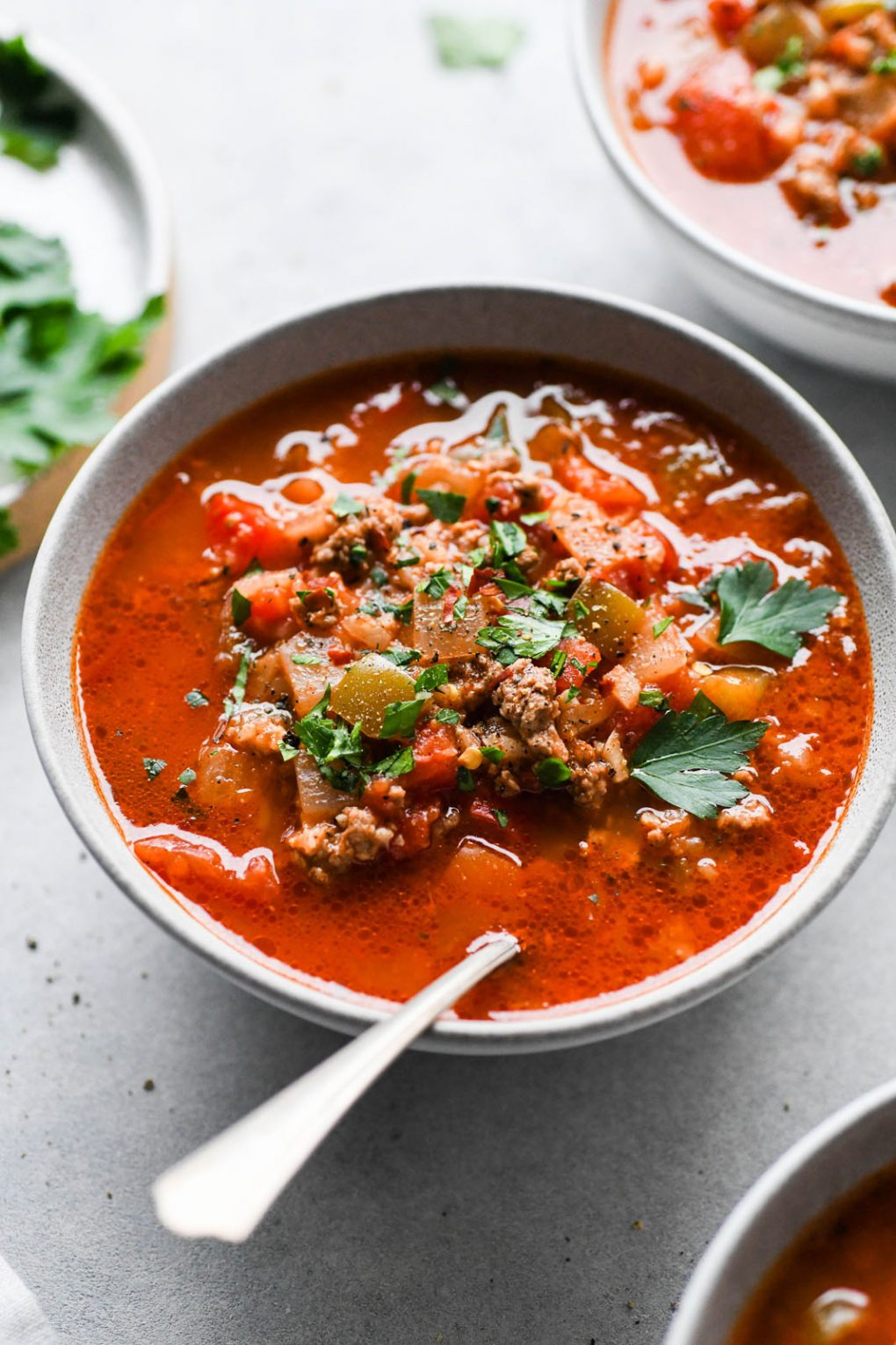 45 degree angle shot of a colorful bowl of stuffed bell pepper soup on a light colored background, topped with fresh parsley and some cracked black pepper.