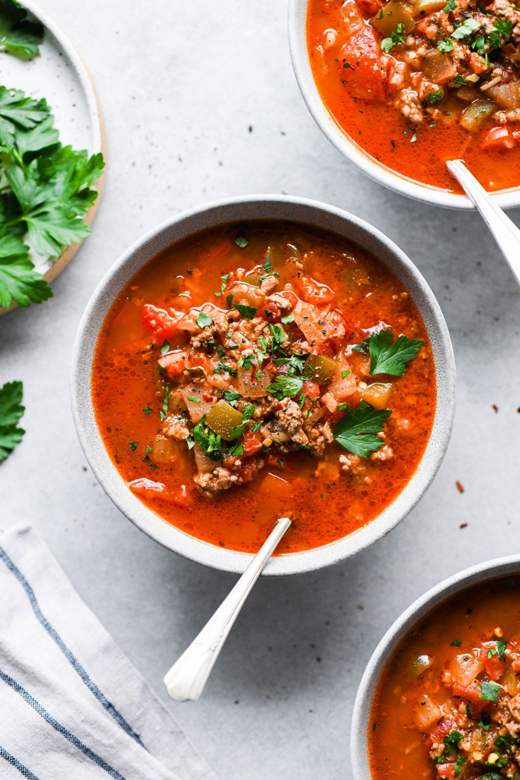 Overhead shot of several colorful bowl of stuffed pepper soup on a light background. On a light background, surrounded by a striped napkin and sprigs of fresh parsley.