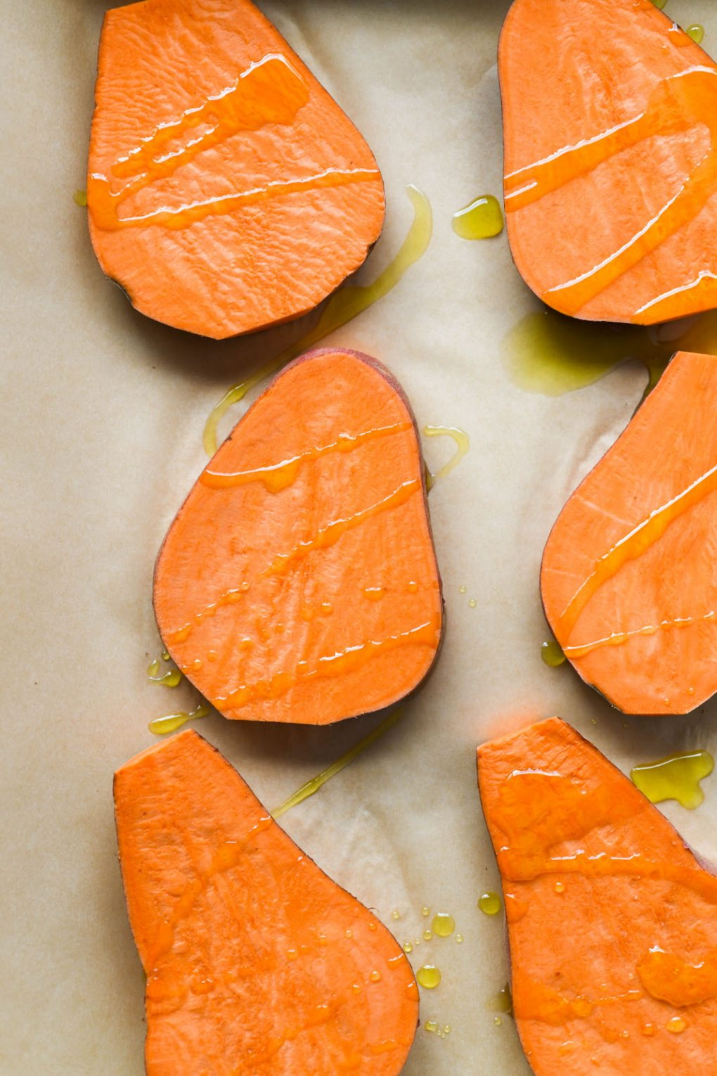 Overhead shot of sweet potato planks drizzled with olive oil on a parchment lined baking sheet.